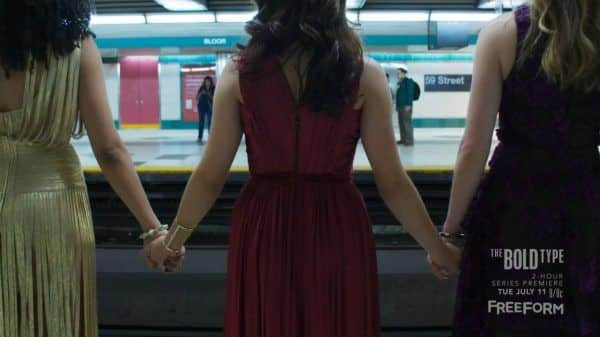 The Women of The Bold Type holding hands before releasing a gnarly scream as a train goes by.