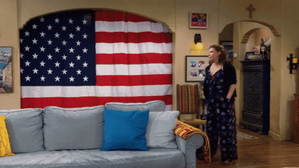 Penelope standing in front of Lydia's new curtains, which are the American flag.