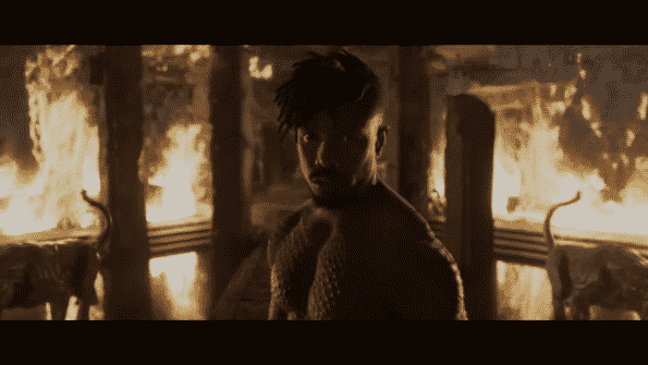 Michael B. Jordan as Killmonger with flames in the background.