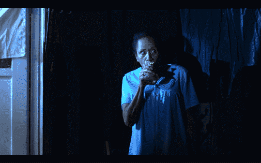 Abuelita, played by Peggy Ann Blow, smoking from a bong.