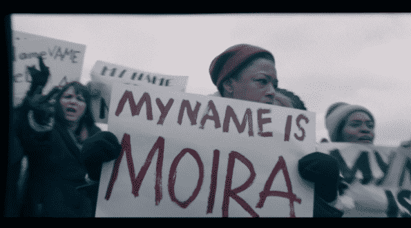"Moira holding a sign which says, ""My name is Moira"""