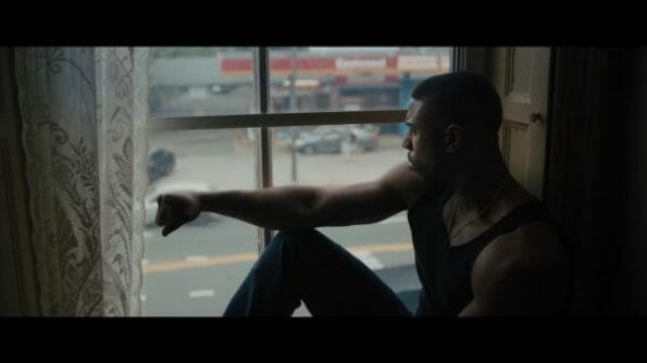 Adonis (Michael B. Jordan) sitting in a window.