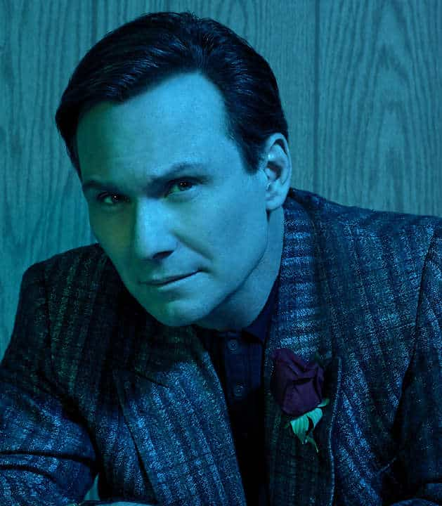 Dan Broderick (Christian Slater) in a suit, with a blue hue over him.