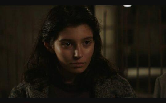 Lila (Gaia Girace) listening to someone.