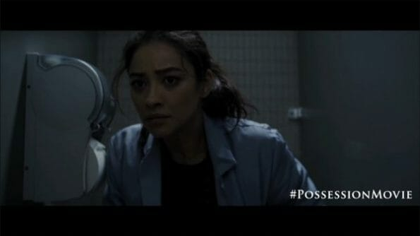 Megan (Shay Mitchell) hearing something while on the toilet.