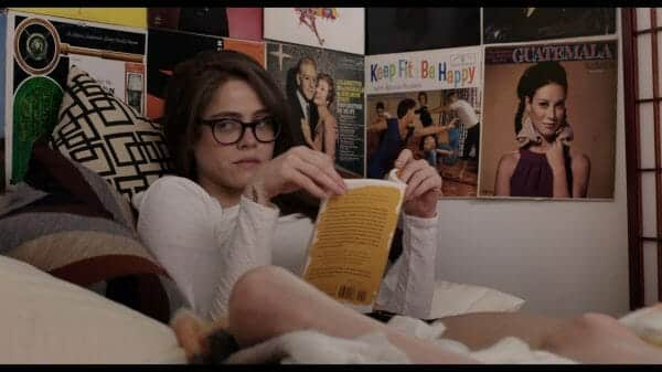 Luce (Olivia Luccardi) reading in bed.
