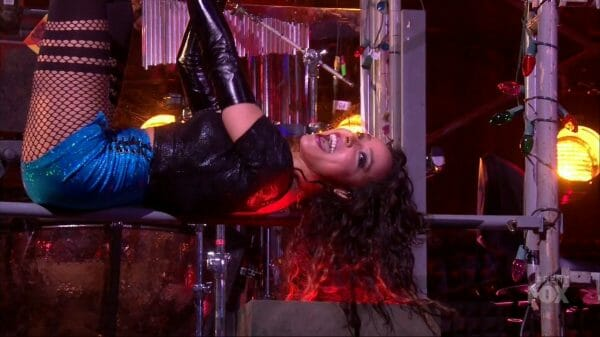 Mimi (Tinashe) hanging from scaffolding.