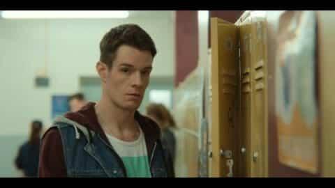 Adam (Connor Swindells) standing by a locker.