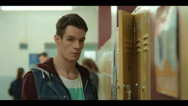 Adam (Connor Swindells) standing by a locker.