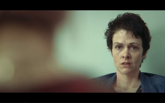 Sarah (Lu Corfield) looking towards Maeve at the abortion clinic.