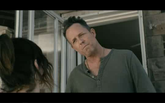 Bobby (Dean Winters) with his head tilted as he talks to Donna.