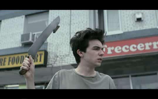 Wayne wielding a blade to cut pizzas.