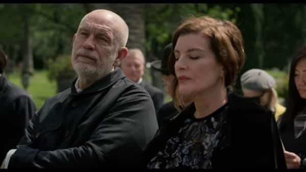 Piers (John Malkovich) and Rhodora (Rene Russo) at a funeral together.