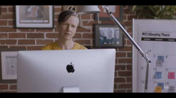Gabe (John Cameron Mitchell) looking over his Mac computer towards Annie.