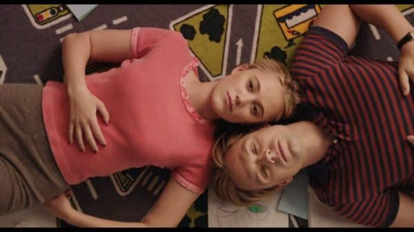 Karen (Maika Moore) and Steve - Adult (Sebastian Stan) laying on the floor together.
