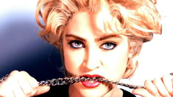 Madonna (Jamie Auld) biting a chain necklace.