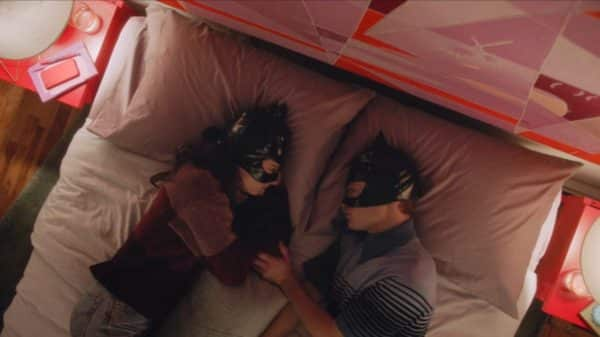 Tiff and Pete in bed, with masks on.