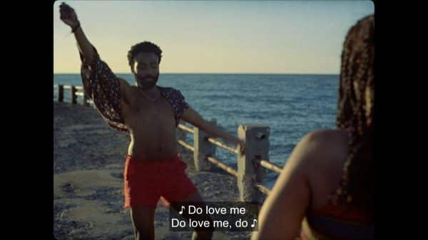 Deni (Donald Glover) singing and dancing to entertain Kofi.