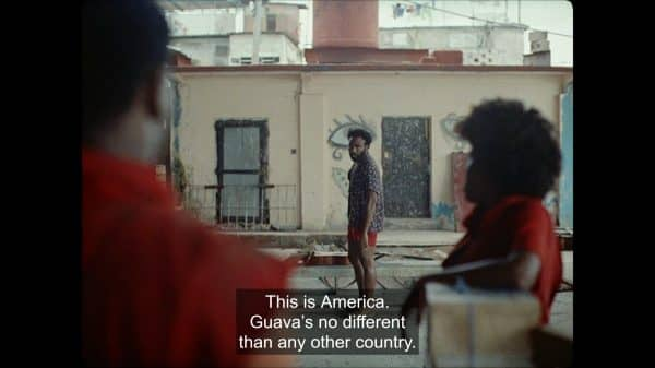 Deni (Donald Glover) noting that going to America wouldn't change things for his co-worker.