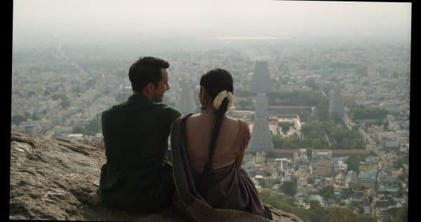 Kris (Christopher Gurusamy) and Valli (Sudgarma Vaithiyanathan) talking to one another, looking out towards the city.