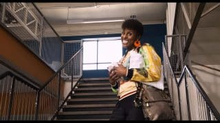 April (Issa Rae) smiling while walking up stairs.