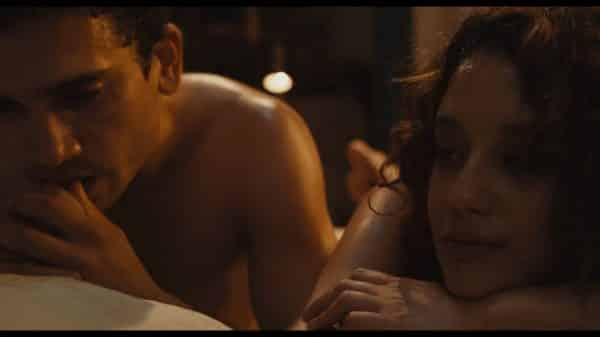 Marcos (Jaime Lorente) and Marta (Maria Pedraza) naked in bed together.