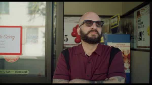 Cuban Tone (Anthony Valderama) standing outside his supermarket.