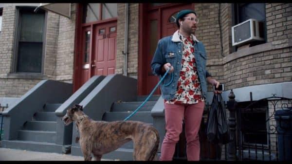 Hipster (David Ebert) walking his greyhound.
