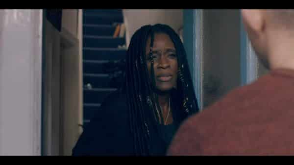 Fran (Sharon Duncan-Brewster) answering her door.