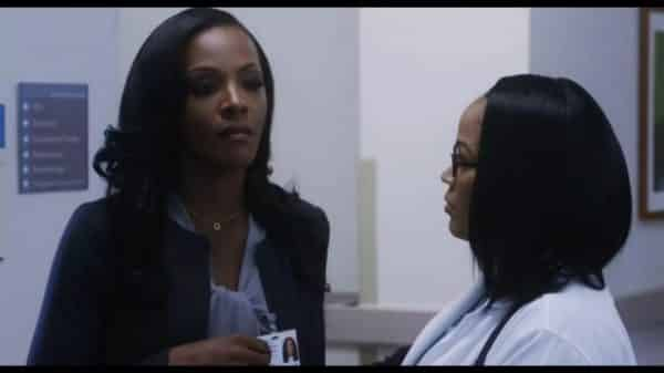Joyce (Dawn Richard) speaking with a colleague.