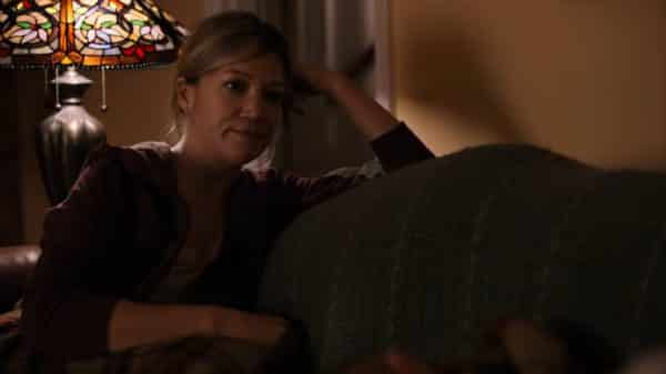 Vicky (October Moore) sitting on the couch talking to Moe.
