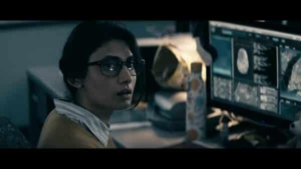 Anika (Ana Sani) at her desk.