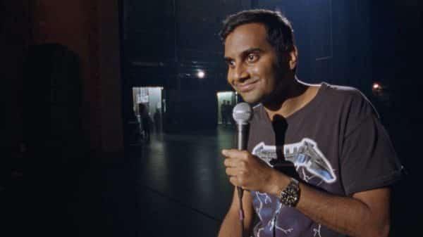 Aziz smiling.