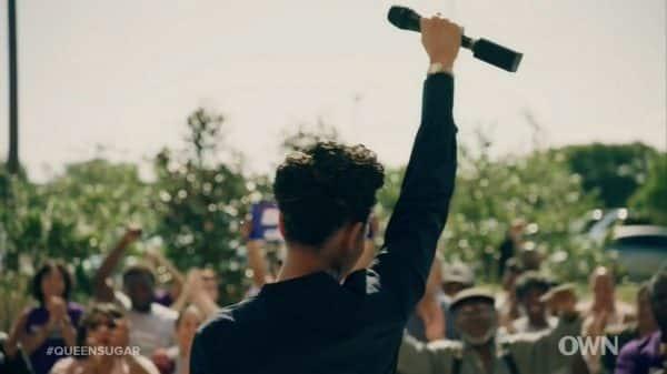 Charley (Dawn-Lyen Gardner) raising a microphone as she announces her candidacy.
