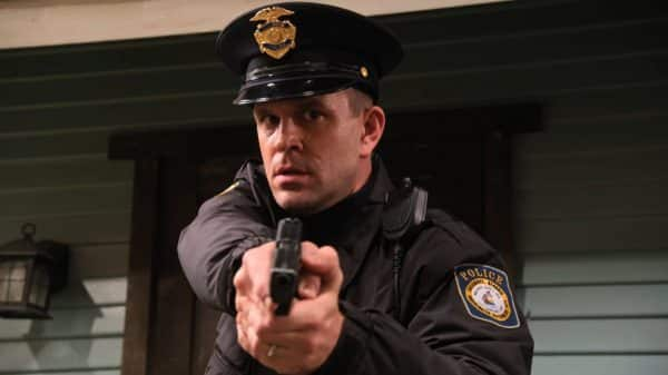 Officer Whitman (John Brotherton) pointing his gun towards Moz's kids.
