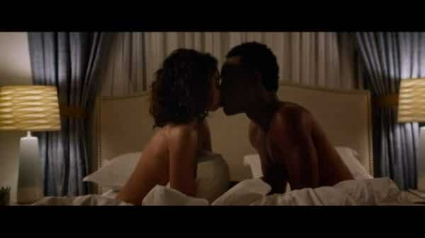 Mara (Sarah Hyland) and Jake (Tyler James Williams) kissing in bed.