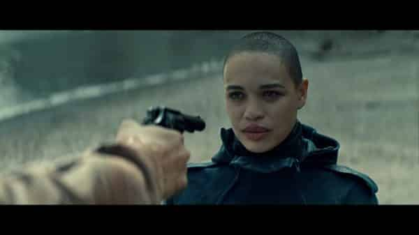 Rya (Cleopatra Coleman) with a gun pointed at her.