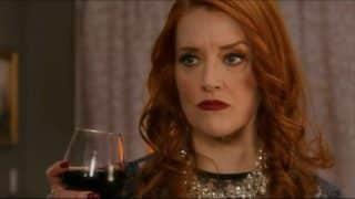 Deirdra (Jonhannah Newmarch) holding a wine glass.