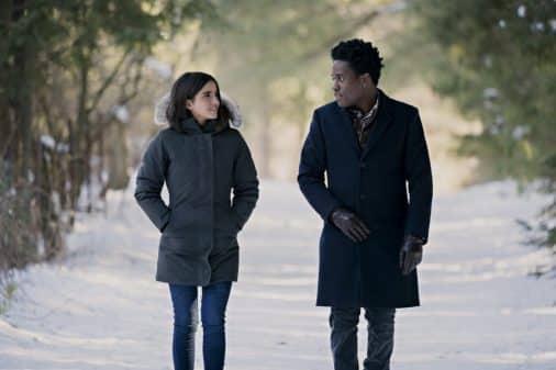 Isabela Moner and Shameik Moore walking in the snow together.
