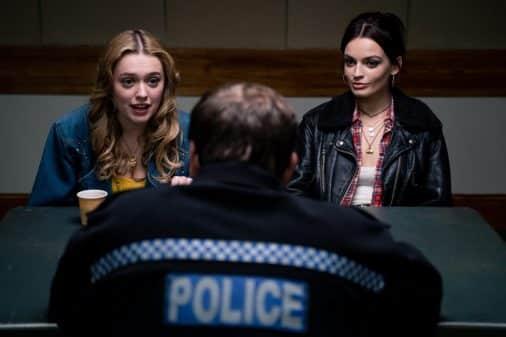 Aimee (Aimee Lou Wood) & Maeve (Emma Mackey) talking to a cop.