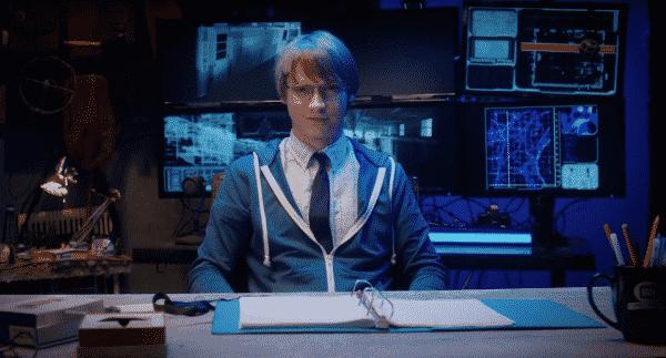 Calum Worthy (Doug) sitting at a desk.