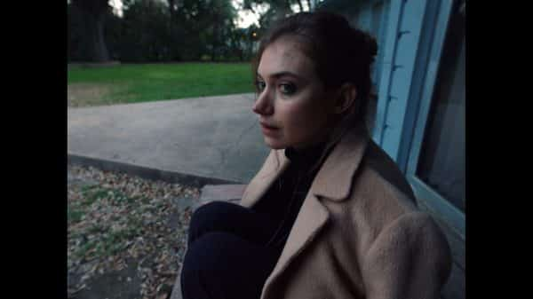Joan (Imogen Poots) sitting on her porch.