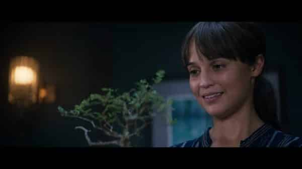 Lucy (Alicia Vikander) smiling as she receives a gift.