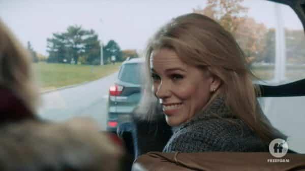 Nancy (Cheryl Hines) smiling over her shoulder.