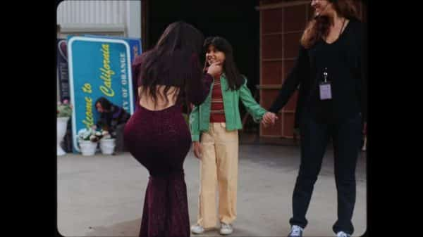 Young Selena (Madison Taylor Baez) being greeted before Christian goes on set.