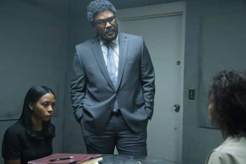 Bresha Webb and Tyler Perry speaking to someone in a interrogation room.