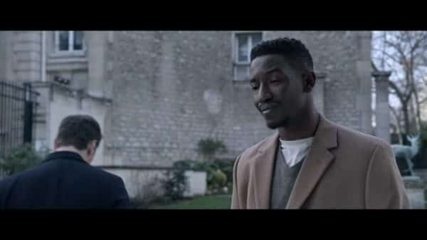 Elijah (Mamoudou Athie) learning his friend will no longer be able to support him financially.