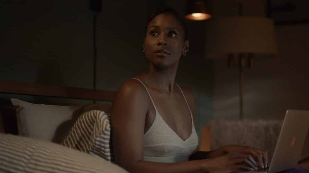 Issa Dee (Issa Rae) working on her computer.
