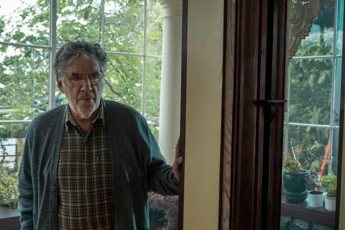 Leonard (Elliott Gould) standing at the entryway of a door.
