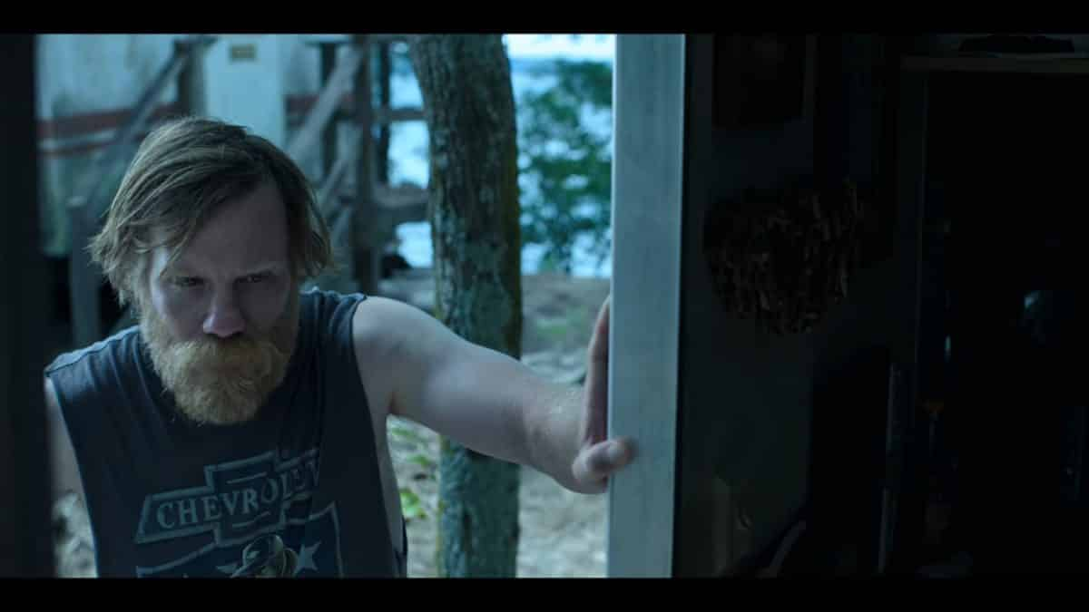 Russ (Marc Menchaca) leaning against a doorframe.